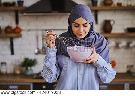 Pretty Arabian Woman Mixing Ingredients In A Bowl With A Whisker
