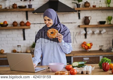 Muslim Woman Having A Video Call On Her Laptop And Showing Ingredients