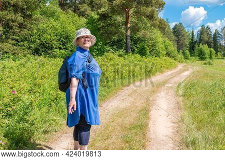Grandmother Goes On A Hike. An Elderly Woman On A Walk In Nature.