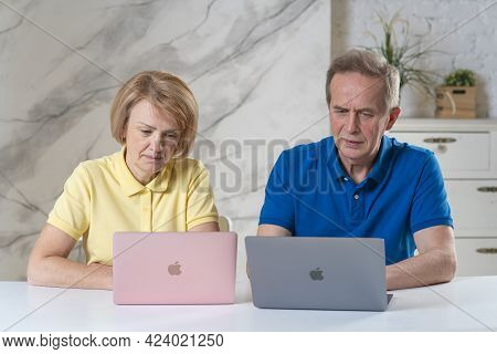 Saint-petersburg, Russia - 06.06.2021: Happy Couple Of Senior Elderly People Working Together On Lap