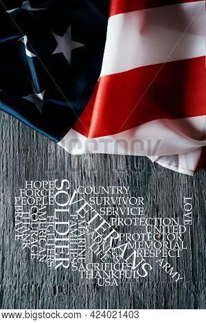 a US flag on a gray rustic wooden surface and a tag cloud, in the shape of the map of the united states, with words to honor the military veterans and their service to the nation