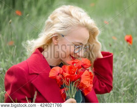 Portrait of a young woman in a poppy field