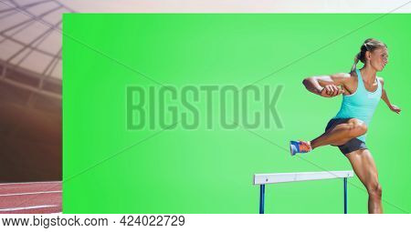 Caucasian female athlete jumping over a hurdle against green screen and sports field in background. sports competition and tournament concept