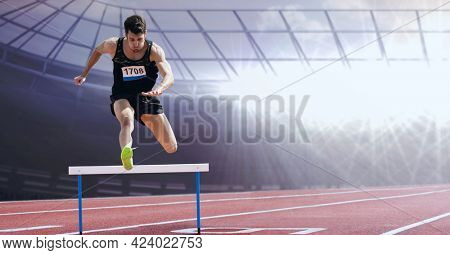Caucasian male athlete jumping over a hurdle against sports field in background. sports competition and tournament concept