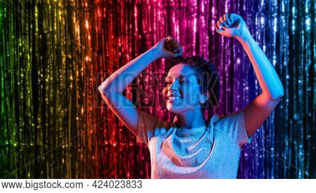 lgbt, clubbing and nightlife concept - smiling young african american woman dancing in ultraviolet neon lights over foil fringe curtain in rainbow colors background