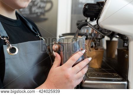 Close-up Of A Baristas Hand Steaming Milk In A Coffee Machine. Making A Latte In A Cafe. Hot Milk Fo