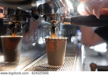Close-up Of A Coffee Machine Making An Espresso. The Coffee Flows Into A Paper Cup Under The Metal S