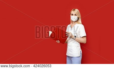 Confident Female Doctor Wearing Protective Face Mask Standing On Red Background With Notebook Or Med