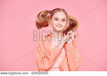 Carefree girl teenager with funny ponytails and in bright trendy clothes jumping on a pink background. Youth style. Fashion.