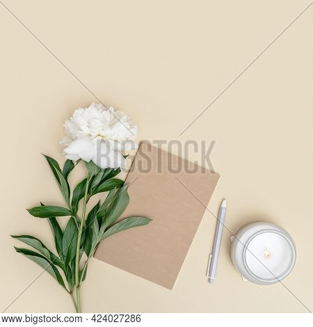 Office Desk With Copybook, Pen, White Peony Flower And Lit Scented Candle In Glass Jar On Beige Back