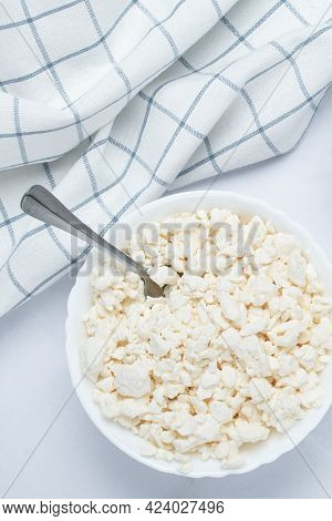 Raw Curd Cheese In A Bowl And Spoon On A White Table. Dairy Product. Russian Cottage Cheese And Napk
