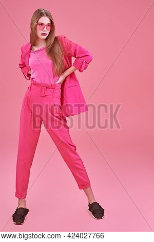 Beautiful fashion model posing at studio in trendy crimson suit and sunglasses on a pink background. Glamorous pink style. Full length portrait.