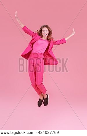 Beautiful fashion model posing at studio in trendy crimson suit on a pink background. Glamorous pink style. Full length portrait.