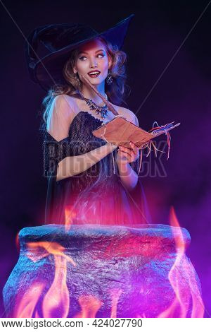 Halloween magic. A beautiful young witch in a hat and elegant dress conjures over a cauldron surrounded by magical fires.