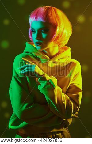 Beauty trends. Portrait of a beautiful girl with bright glitter makeup and pink hair posing in mixed color neon light. Makeup cosmetics and hairstyle.