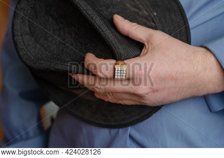 A Middle-aged Man In A Blue Shirt Clutches His Hat. A Hand With A Gold Ring On The Index Finger Hold