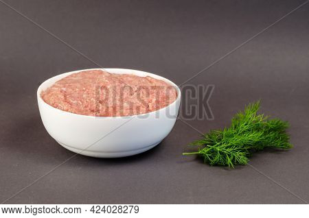 Raw Ground Meat And Green Dill On A Gray Background. White Ceramic Bowl With Minced Turkey. Food, In