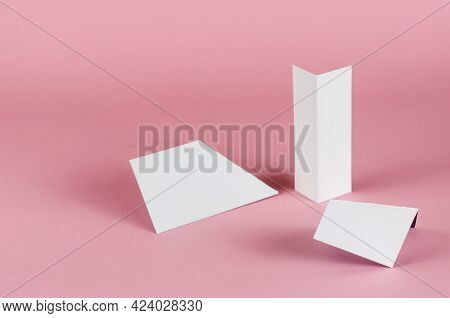 White Abstract Geometric Shapes On Pink Background. Three Random Geometric Shapes On A Colored Backg