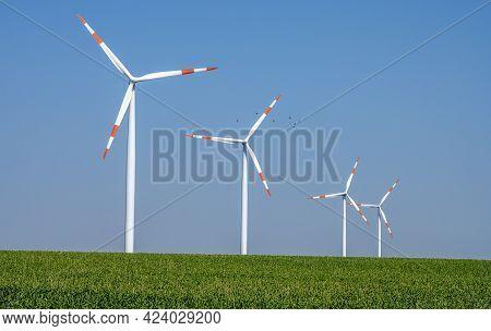 Modern Wind Turbines In A Grainfield Seen In Germany