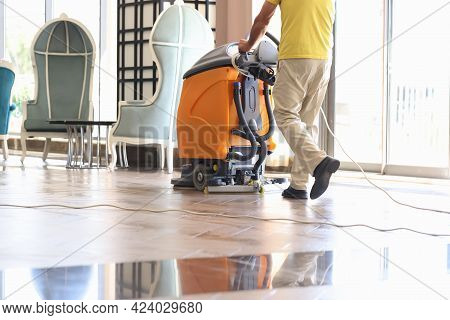 Janitor Is Cleaning Hall With Washing Vacuum Cleaner Closeup