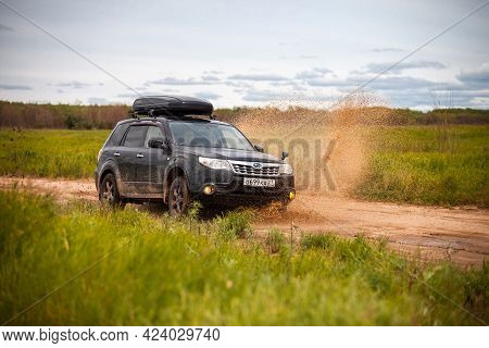 Nikolaevka, Russia - June 23, 2020: Black Subaru Forester Moving At Dirty Forest Road Making A Lot O