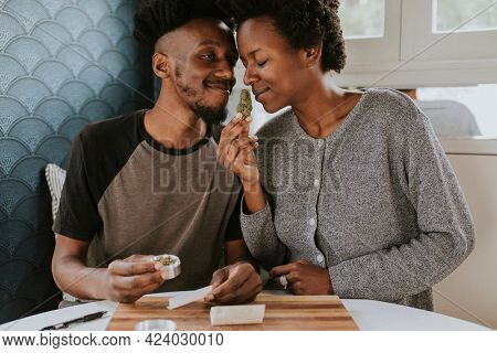 A couple rolling a joint