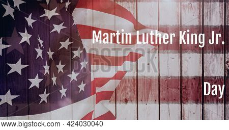 Happy martin luther king day text and waving american flag on wooden background. martin luther king day template background design concept