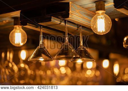 Martini Glasses Hang Upside-down In The Bar Between Several Lamps With Warm Light In The Restaurant
