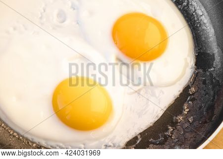Two Bright Round Raw Yolks In Whites With Edge Cracks In A Frying Pan. Cooked Tender, Soft Fried Egg