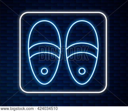 Glowing Neon Line Slippers Icon Isolated On Brick Wall Background. Flip Flops Sign. Vector