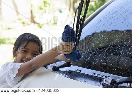 Closeup Hand Of Asian Little Girl Holding A Cloth In Her Hand To Help Wipe The Windshield Wiper Car
