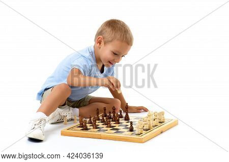 Cute Little Boy Sitting On The Floor Playing Chess, Thoughtful Blond Stylish Boy Wearing White Shirt