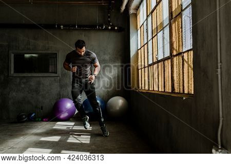 Sportive man doing a side to side jump in a gym