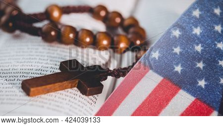 American flag against cross rosary over bible. american patriotism and religion template background design concept