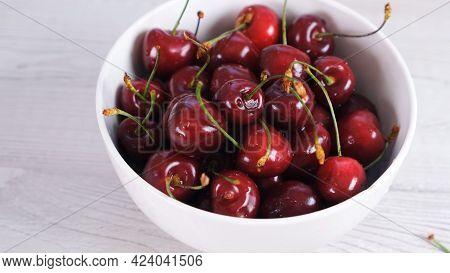 Fresh Cherry On Plate On Wooden White Background. Fresh Ripe Cherries. Sweet Cherries