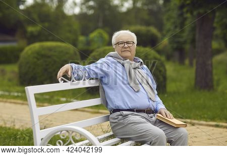 Senior Man Sits On A Bench And Reads A Book. An Elderly Man With White Hair Is Resting On A Park Ben