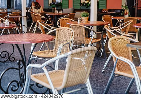Cozy Outdoor Cafe In The Open Air. Wicker Chairs And Tables In An Empty Open-air Restaurant. Calm An