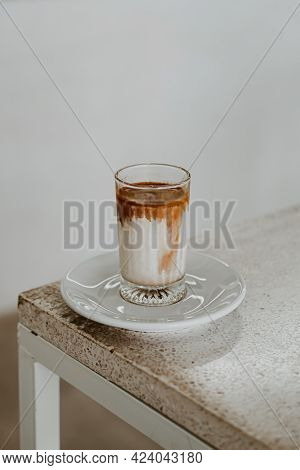 Dirty Coffee In A Glass Placed On A White Table With Sunlight In The Morning Time.