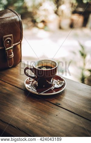 Hot Americano Coffee Or Black Coffee In A Brown Glass Placed On A Wooden Table With Sunlight In The