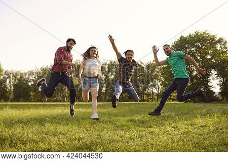 Happy Young Friends Jumping Together Outdoors. Group Of People Having Fun During Summer Vacation In