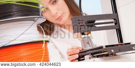 Young female designer working on a prototype device on a 3D printer