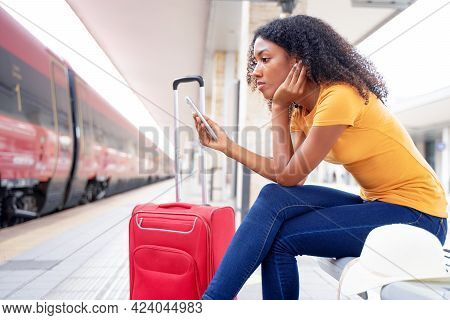 Afro Woman Waiting For The Train In Station Platform Using Cell Phone