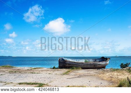 Landscape With Abandoned Old Fishing Boat By The Bay