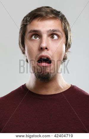 Portrait of young man with silly grimace isolated over background