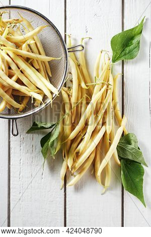 Yellow Wax Beans On A White Wooden Table.
