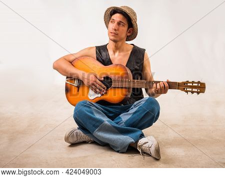 Handsome Young Man In Leather Vest With Guitar In Studio Shot