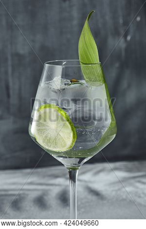 Asian Gin tonic cocktail for lifestyle design. Summer cocktail asian concept background. Gin tonic drink with lime slice and banana leaf. Cocktail in wine glass with palm leaf shadow