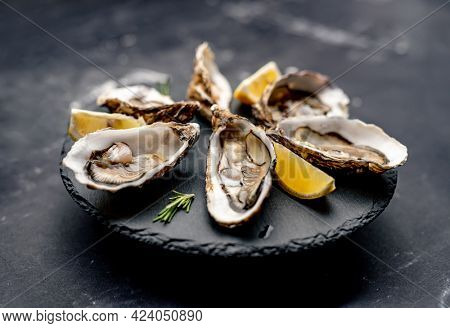 Oysters with lemon served on black round platter. Luxury delicatessen seafood