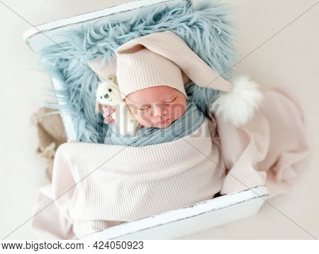 Portrait of newborn baby boy wearing knitted hat sleeping on white small designed bed under blanket and holding toy. Adorable infant child napping during studio photoshoot