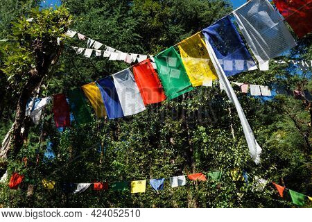 Buddhist prayer flags lungta with Om Mani Padme Hum Buddhist mantra prayer meaning Praise to the Jewel in the Lotus on kora around Tsuglagkhang complex. McLeod Ganj, Himachal Pradesh, India